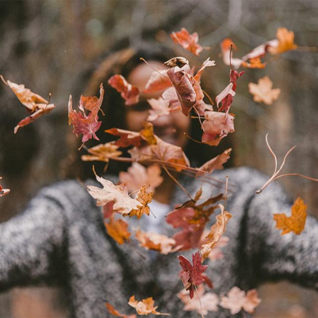 Eine Frau vertreibt den Herbstblues beim Spaziergang im bunten Blätterwald. So fühlt sie sich nicht mehr antriebslos und abgeschlagen.